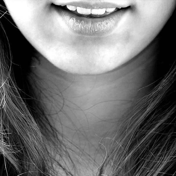 black and white image of a woman's chin and neck