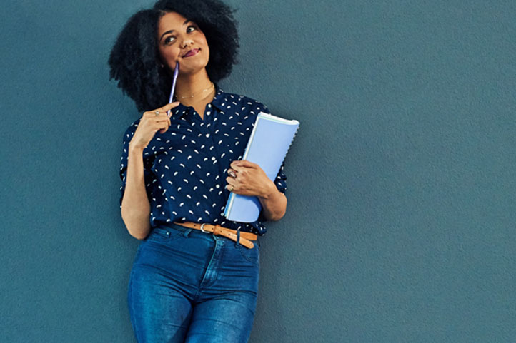 a curly woman standing with a notebook and pen in her hand